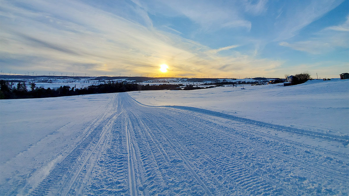 winter snowmobile trail heading into the sunset
